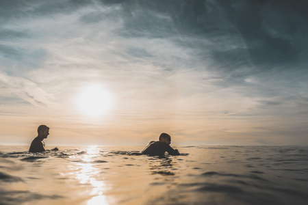 Two surfer friends patiently wait for a wave over the calm sea at sunset. Extreme water sports and outdoor active lifestyle. Vintage filter with soft style Stock Photo