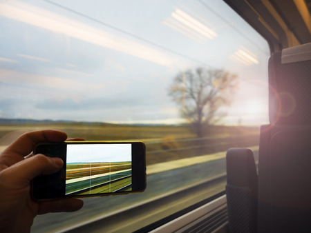 Subjective shoot of one hand taking a picture of the landscape through the window of the moving train with a smart phone. Dynamic image due to motion blur. Sunlight creates soft and romantic effect