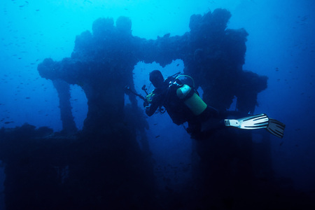 diver taking pictures of the remains of a sunken ship. The old remains of the ship are surrounded by lots of small fish and the blue and turbid water gives an aura of mystery Фото со стока