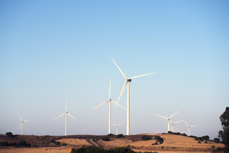 set of windmills produce clean energy in a wind farm. They are in a rural environment surrounded by crops and trees, the sky is clean and clear. Copy space Banco de Imagens