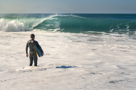 Man on the seashore prepares to surf, wears a black neoprene suit and in his hand has a blue bodyboard. the water covers him to the knee while watching a huge wave breaking Stock Photo