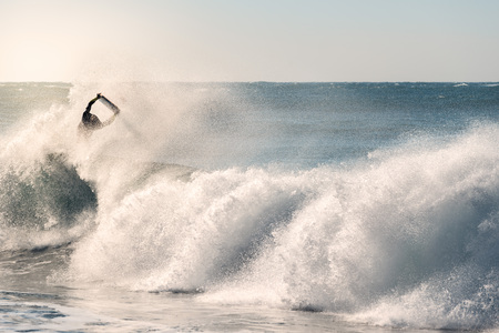 man surfing jumps a great wave that breaks with a lot of power and energy, the sunlight reflects golden on the turquoise surface of the sea and in the plumes of water that the wind raises Stock Photo