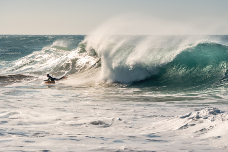 man surfing a huge wave that chases him, the sunlight reflects golden on the turquoise surface of the sea and on the foam and the plumes of water that the wind blows