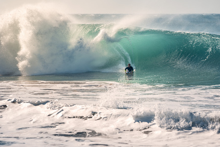 man surfing the barrel of a perfect wave that breaks with a power and energy, the sunlight reflects on the turquoise surface of the sea and in the huge pile of foam, the wind lifts up plumes of water Stock Photo