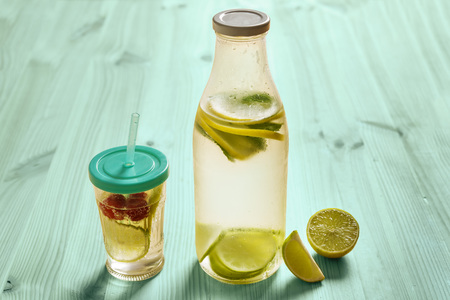 glass bottle and glass with lid and cane, with cold water and slices of lemon, lime, berries and mint, are illuminated by sunlight on a turquoise wooden table with some pieces of citrus