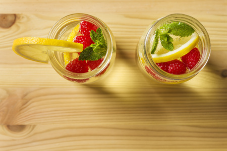 overhead shot of two glass jars with cold water, lemon slices, red berries and mint leaves on a wooden table, are illuminated by sunlight. Summer refreshment background with citrus, copy space