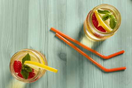 flat lay of two drink canes and two glass jars with refreshing cold lemonade water, lemon, red berries and mint on a green wooden table lit by sunlight, Summer citrus refreshment background Copy space