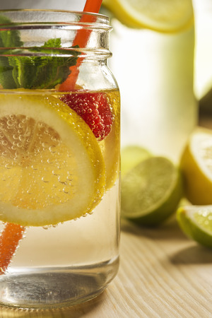 glass jar and bottle lit by sunlight with refreshing cold lemonade water, lemon slices, red berries, mint leaves and drinking canes on a wooden table. Summer citrus soda background, vertical photo Stock fotó