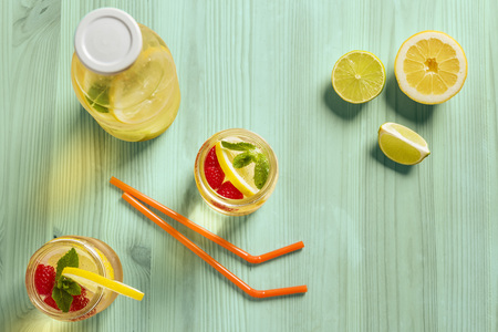 top view, two glass jars and a bottle with refreshing cold lemonade water, lemon, red berries and mint on a green wooden table with citrus lit by sunlight, Summer refreshment background Copy space