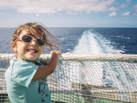 little girl with sunglasses caught at the railing of the cruise ship in which she travels smiles at the camera, the wind moves her hair and the white foam from the ship's wake moves through the ocean