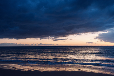 spectacular sunset on the beach, the blue sky is covered in storm clouds and it is orange and yellow on the horizon