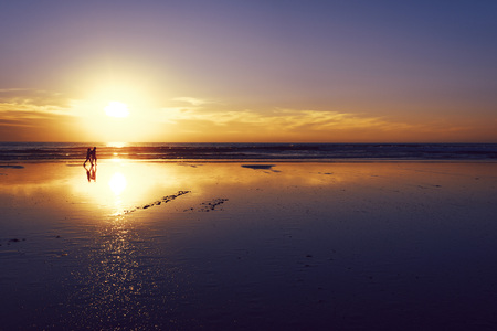 silhouette of a couple strolling on the beach, walk at sunset over the reflection of the sun on the wet sand