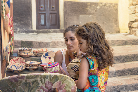 mother and daughter buying handmade souvenirs at a street stall in Castelsardo, Sardinia, Italy 写真素材