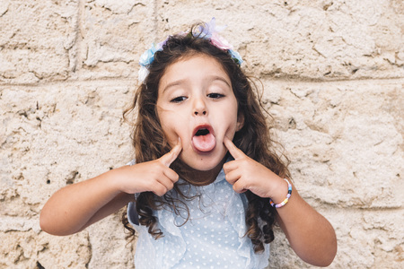 little girl making fun with her tongue, is in front of a stone wall and wears a blue dress and a flower headband