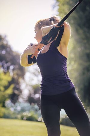 vertical photo of an athletic woman training with fitness straps, during functional workout in a sunny outdoor park in the morning