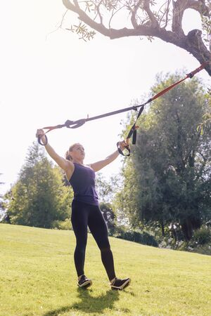 vertical photo of an athletic young woman training with fitness suspension straps, during functional workout in a sunny outdoor park in the morning Stok Fotoğraf