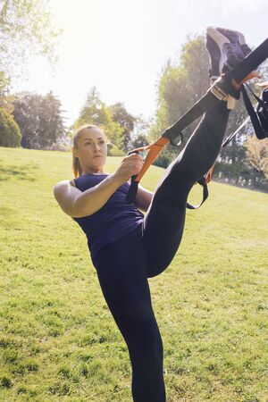 vertical photo of a beautiful young woman doing exercises outdoors under a tree, fitness girl workout with suspension straps at the morning in a sunny park Stok Fotoğraf