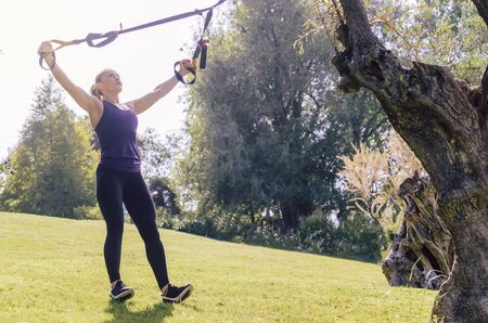 athletic young woman training with fitness suspension straps, during functional workout in a sunny outdoor park in the morning 免版税图像
