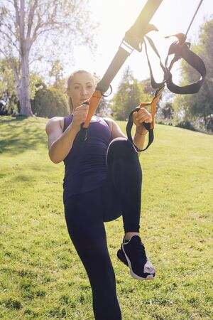 vertical photo of a young beautiful woman doing exercises outdoors under a tree, fitness girl workout with suspension equipment at the morning in a sunny park Stok Fotoğraf