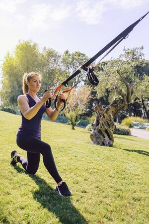 vertical photo of an attractive young woman training fitness with suspension straps, she is outdoors during functional workout