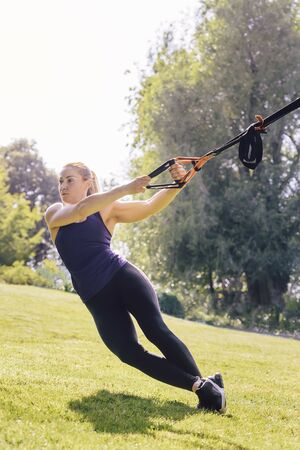 vertical photo of a young beautiful blonde woman using suspension straps, functional workout in a sunny outdoor park in the morning Stok Fotoğraf