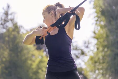 athletic woman training with fitness straps, during functional workout in a sunny outdoor park in the morning Stok Fotoğraf