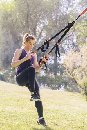 vertical photo of a strong young woman training with fitness suspension straps, during functional workout in a sunny outdoor park at the morning Stok Fotoğraf