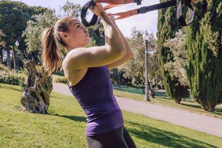 strong young woman training biceps with fitness suspension straps, during functional workout in a outdoor park Stok Fotoğraf