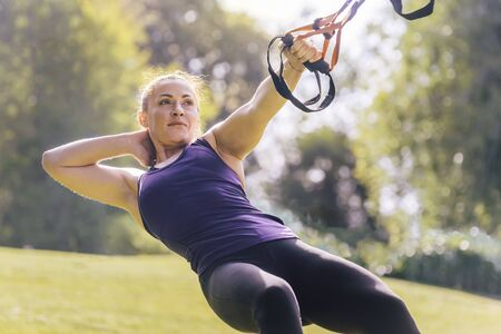 attractive young woman training fitness with suspension straps, during functional workout in a sunny outdoor park in the morning
