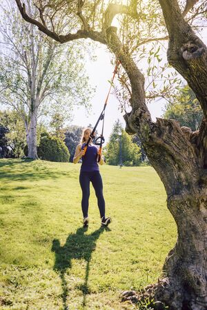 vertical photo of a beautiful young woman training outdoors under a tree, fitness girl workout with suspension equipment at the morning in a sunny park Stok Fotoğraf