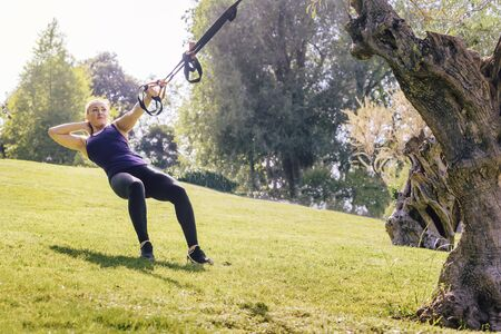 pretty fitness woman training with suspension straps, during functional workout in a sunny outdoor park in the morning