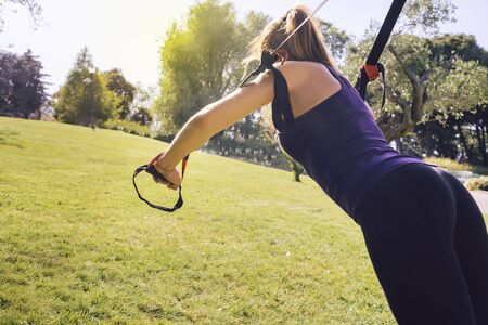 young beautiful blonde woman using suspension straps, exercise routine outdoors at the evening in a sunny park