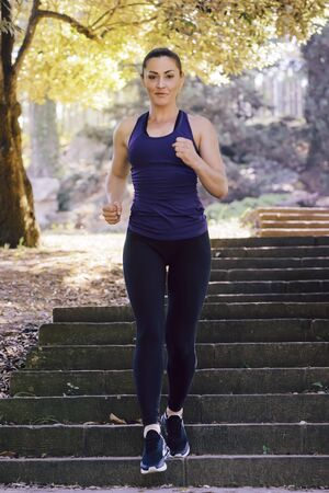 front view of young sports woman running downstairs during fitness workout at the park at the morning with sunlight, sport and healthy lifestyle concept, vertical photo