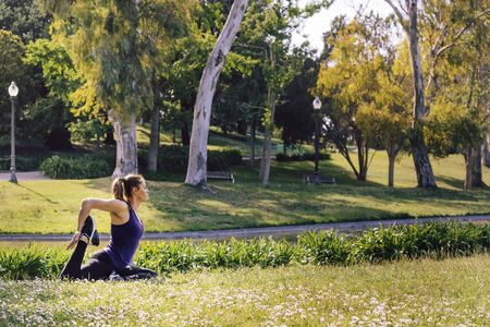 young sports woman doing meditation yoga flexibility exercises and relaxing outdoors in the park, modern healthy lifestyle and sport concept Stok Fotoğraf