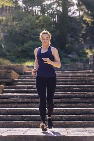 young sporty woman running downstairs in the afternoon on the stairs of the park, morning workout outdoors, sports and healthy lifestyle