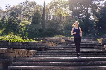 young sports woman running downstairs in the morning on the stairs of the park, morning workout outdoors, sports and healthy lifestyle