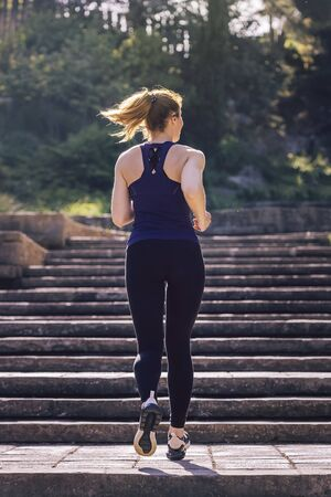 young sporty woman running upstairs in the morning on the stairs of the park, morning workout outdoors, sports and healthy lifestyle