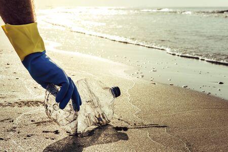 Hand eines Mannes mit Handschuhen, der Plastikflaschen aufhebt, die den Strand verschmutzen, am Ufer säubern, Kampagne für ein sauberes Freiwilligenkonzept Standard-Bild