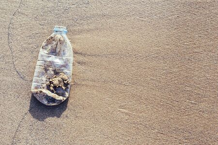 background of a plastic bottle lies on the sand of the beach and pollutes the sea and the marine life, concept of pollution control of the oceans by plastic, copy space for text