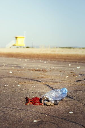 vertical photo of a plastic bottle and garbage lies on the sand of the beach polluting the sea and the marine life, concept of pollution control of the oceans by plastic