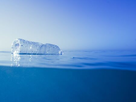 plastic waste at the ocean, a plastic bottle floating in the Mediterranean sea at the water surface, environmental problem with plastics pollution, copy space for text Imagens