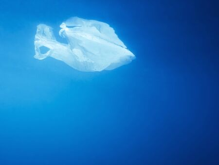 plastic waste at the ocean, a plastic bag in the Mediterranean sea floating at the blue water surface view from underwater, environmental problem with plastics pollution, copy space for text Imagens