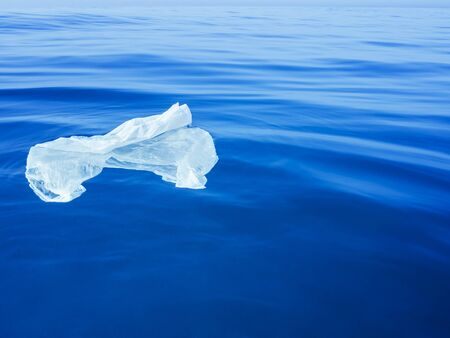plastic waste at the ocean, a plastic bag in the Mediterranean sea at the blue water surface, environmental problem with plastics pollution, copy space for text