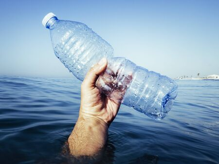 plastic waste at the ocean, hand coming out of the water holding a plastic bottle in the Mediterranean sea, environmental problem with plastics pollution, copy space for text