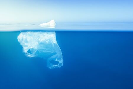 plastic waste underwater, a plastic bag at the Mediterranean sea in the blue water surface like an iceberg, environmental problem. Copy space for text