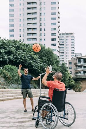 joyful handicapped man in wheelchair playing basketball with a friend with ball, concept of adaptive sports and physical activity, rehabilitation for people with physical disabilities, vertical photo