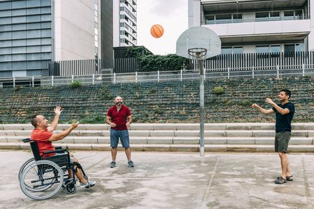 joyful disabled man in wheelchair playing basketball with friends with a ball, concept of adaptive sports and physical activity, rehabilitation for people with physical disabilities 写真素材