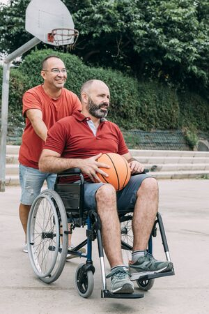 man pushing the wheelchair to play basketball with his handicapped friend, concept of adaptive sports and physical activity, rehabilitation for people with physical disabilities, vertical photo 写真素材