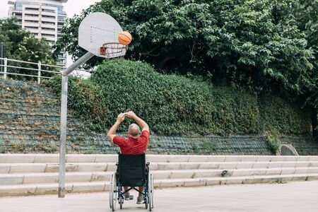 handicapped man playing basketball alone in the city, concept of adaptive sports and physical activity, rehabilitation for people with physical disabilities
