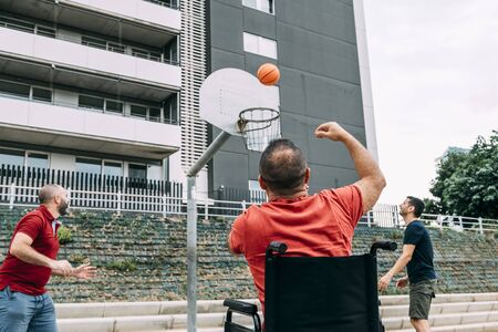 joyful disabled man in wheelchair throwing the ball to basket with two friends, concept of adaptive sports and physical activity, rehabilitation for people with physical disabilities